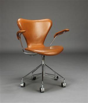 Arne Jacobsen. 7'er kontorstol med armlæn, skal af formspændt krydsfinér betrukket med cognacfarvet skind, stel af forkromet stålrør, højdejusterbar. Fremstillet hos Fritz Hansen, model 3217. Fremstår med lettere slitage på armlæn.