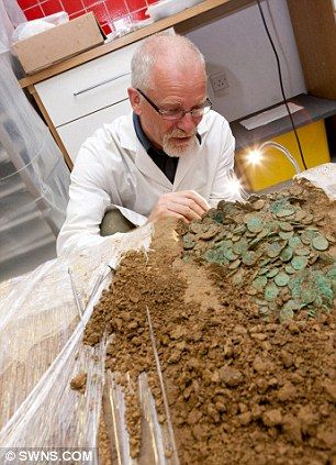 Neil Mahrer, Conservator for the Jersey Heritage Museum inspects some of the coins uncovered in Europe's largest hoard of Iron Age coins wor...