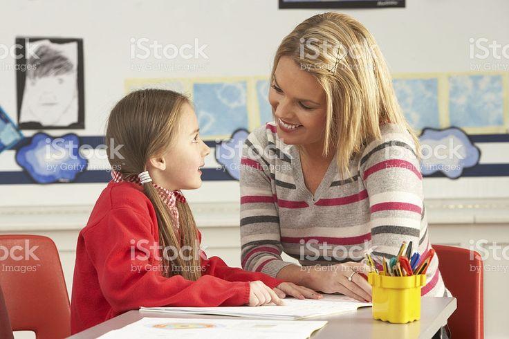 Weibliche Grundschule Schüler und Lehrer Arbeiten am Schreibtisch – lizenzfreie Stock-Fotografie