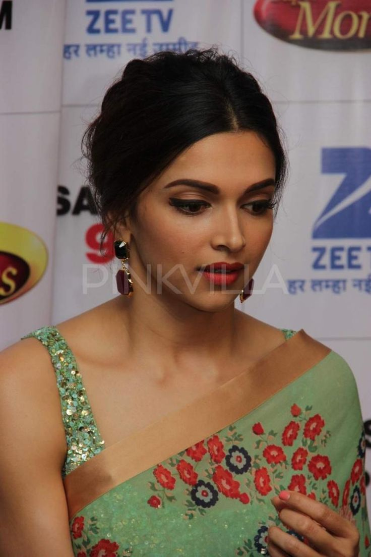 Retro eyeliner and red lips, minimal blush. Hair and sari are also modern retro, but not as streamlined as the makeup.
