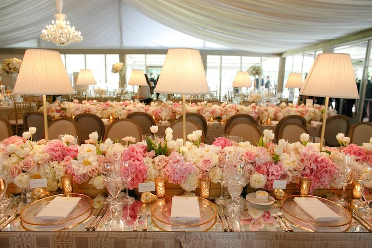 The head table was adorned with tall lamps and a pink floral runner. Photography: Karlisch Studio. Read More: http://www.insideweddings.com/weddings/southern-chic-wedding-in-oklahoma-with-performance-by-boyz-ii-men/697/