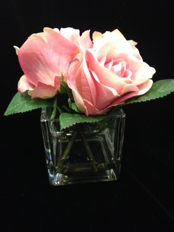 The pink rose arrangement shown in it glass vase.