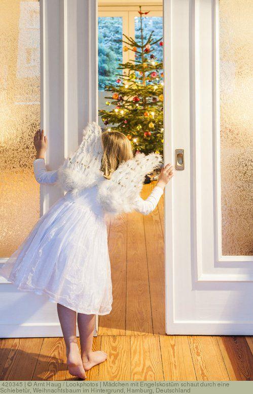 Mädchen mit Engelskostüm schaut durch eine Schiebetür, Weihnachtsbaum im Hintergrund, Hamburg, Deutschland