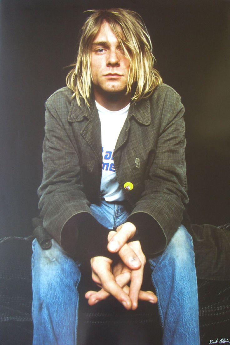 Embracing a worn second-hand look, Kurt Cobain wears jeans, a graphic t-shirt and fingerless gloves with a lightweight jacket, adorned by buttons.