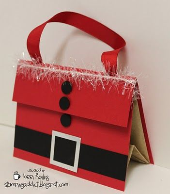 """This is a simple little gift bag decorated to look like Santa.      The bag is just a basic brown paper lunch sack. Here are some dimensions for you:    Back red cardstock piece is 5 1/2 x 6 1/4. The 5 1/2"""" side is scored at 2"""" and that will make the flap that flips over the top.    Front red cardstock piece is 5 1/2 x 4""""    Black belt is 5 1/2"""" x 1"""" and silver buckle is 1 3/8"""" square    Black buttons are 1/2"""" circles    I tied some tinsel around the top. Bag is shut with velcro.    Ribbon…"""