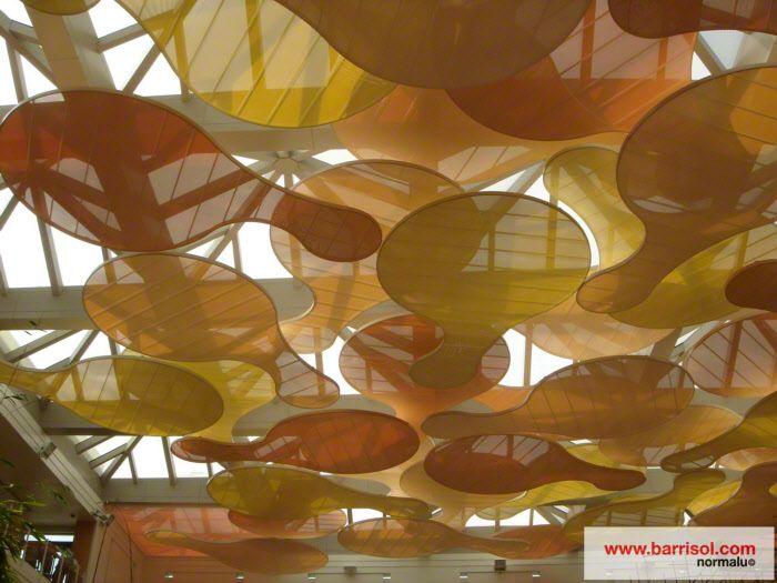 Plafond suspendu Barrisol aux formes modulaires arrondies et installées en superposition pour créer un jeu de lumière et de perspective avec l'utilisation de toiles PVC acoustique laissant passer la lumière