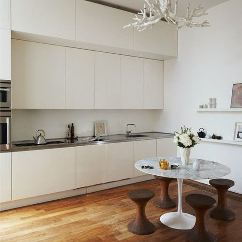 Minimal kitchen-diner    The kitchen has a minimal, clean look. The fitted units are made from spray-painted MDF - designed to take up as little space as possible. The splashback is simply wood, spray-painted to a glossy finish.