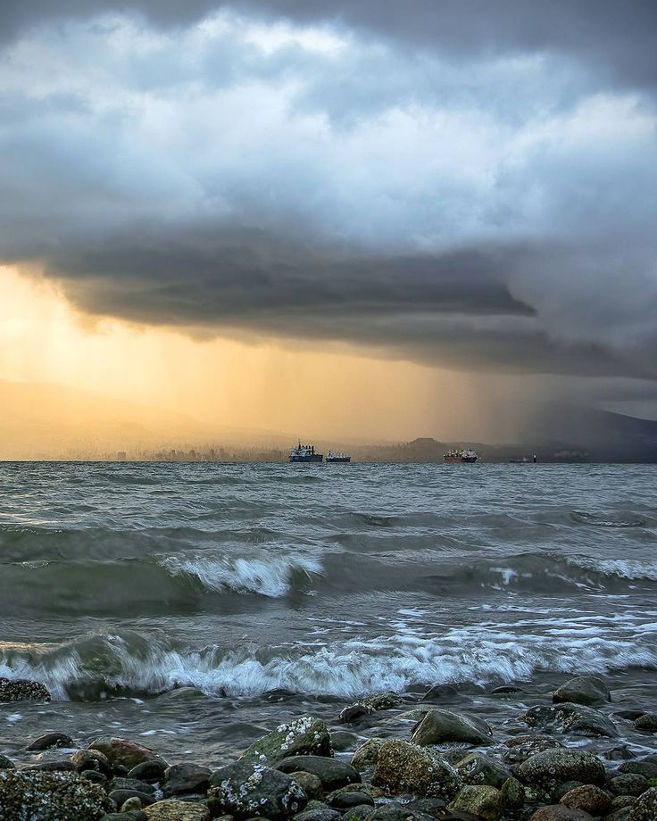 West Coast Sun Shower  . Storm clouds unleash loads of rain over the north shore mountains. The setting sun breaks through the clouds and lights up West Vancouver. Looking over English Bay to Dundarave and Ambleside getting drenched. Captured from the rocky shores of Acadia Beach in Vancouver British Columbia Canada  Throwback to June 14 2016 . #BCFStormWatching  . . . . . . #WestVan #WestVancouver #Vancouver @Vancouver_Canada #VeryVancouver #VisitaVancouver #CuriocityVan #VancityFeature…