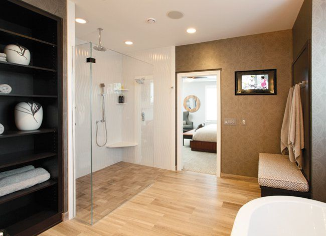 Clean, strong lines and high tech features and electronics, including digital remote controls for the shower, an air masseur soaking tub, and a flat-screen television, dominate this renovated master bath.