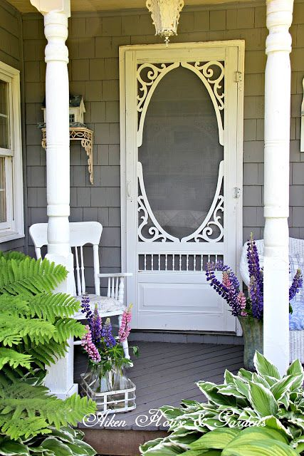 All the right ingredients for an inviting front porch: a vintage screen door, comfy seating, one-of-a-kind accessories and lots of greenery.