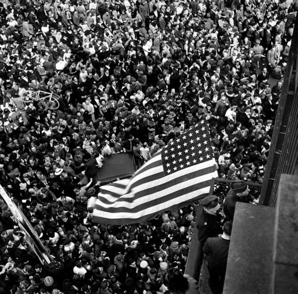 An American flag waving over an excited crowd,  celebrating in a Paris street as VE (victory in Europe) is confirmed: American Flags, Wwii, Flags Waves, Paris Street