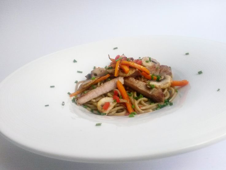 Espagueti de chía con lomo de cerdo al ajillo, todo acompañado de pimentones y champiñones salteados.