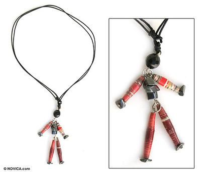 """Francis Oliveira, """"Art for me today is an instrument of transformation.""""  Set with hematite stones, this whimsical puppet carries a message of happiness. Francis Oliveira crafts the doll from recycled magazines and adds a faceted bead for the head. The pendant is worn on an adjustable necklace of black cotton cords. $20.00."""