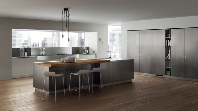 A trendy colour for this composition: stained look lacquered doors in Stained Steel for the island and cabinets, Light Grey matt lacquered doors for the work area and open-fronted tall units, stainless steel for worktops. Coloris tendance pour cette composition : portes laqué effet oxydé Stained Steel pour l'îlot et les armoires, portes laqué mat Gris Clair pour la zone de travail et les colonnes ouvertes et les plans de travail en acier inoxydable.