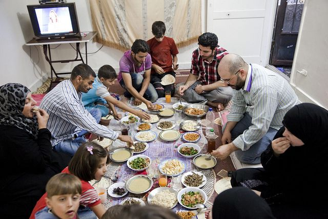 """Day 9: Ahmed, 48, (left) and his family share the #Iftar meal during Ramadan in #Cairo, #Egypt. Ahmed spent 4 months in jail in #Homs, #Syria before fleeing to #Turkey with his wife and 2 children after their home was destroyed. """"I feel like I'm in heaven here because I spent the last 3 Ramadan's under gunfire,"""" he says. Photo and text by Shawn Baldwin for UNHCR"""