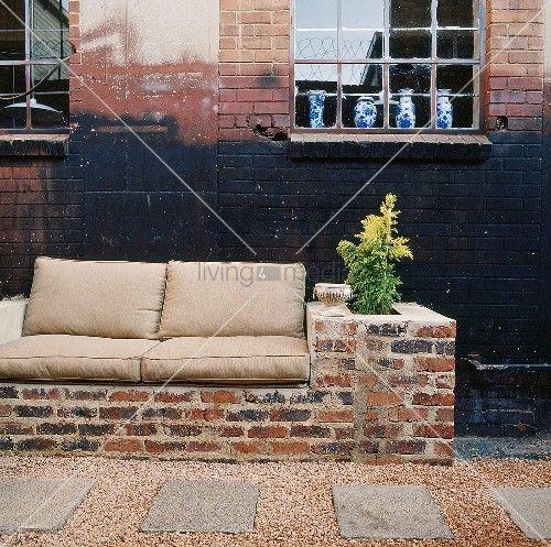 Eine gemauerte Couch mit sitzpolster vor Backsteinwand