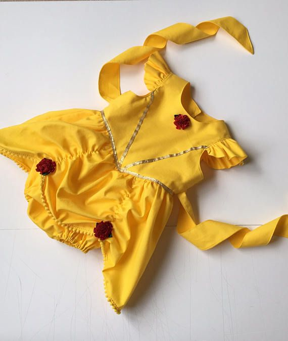 The Belle Romper is perfect for the little girl who wants to wear princess attire all day, everyday. This romper is perfect for playtime, Disney vacations, dress up, Halloween costumes or even a trip to the grocery store. The Belle romper is constructed of cotton fabric. It also features a full skirt with rosettes and flutter sleeves with gold trim on the bodice and at the waist. It has a button back, with a sash at the waist to allow for growth.