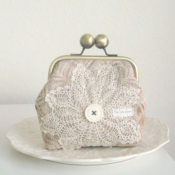 I made this one of a kind lovely clutch with two layers of cream and beige vintage doilies and linen fabric. The clutch is adorned with a