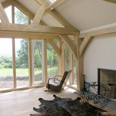 Living Room with Exposed Oak Queen Post Truss in New Build Oak Frame House in Cornwall. Carpenter Oak | Roderick James Architects.