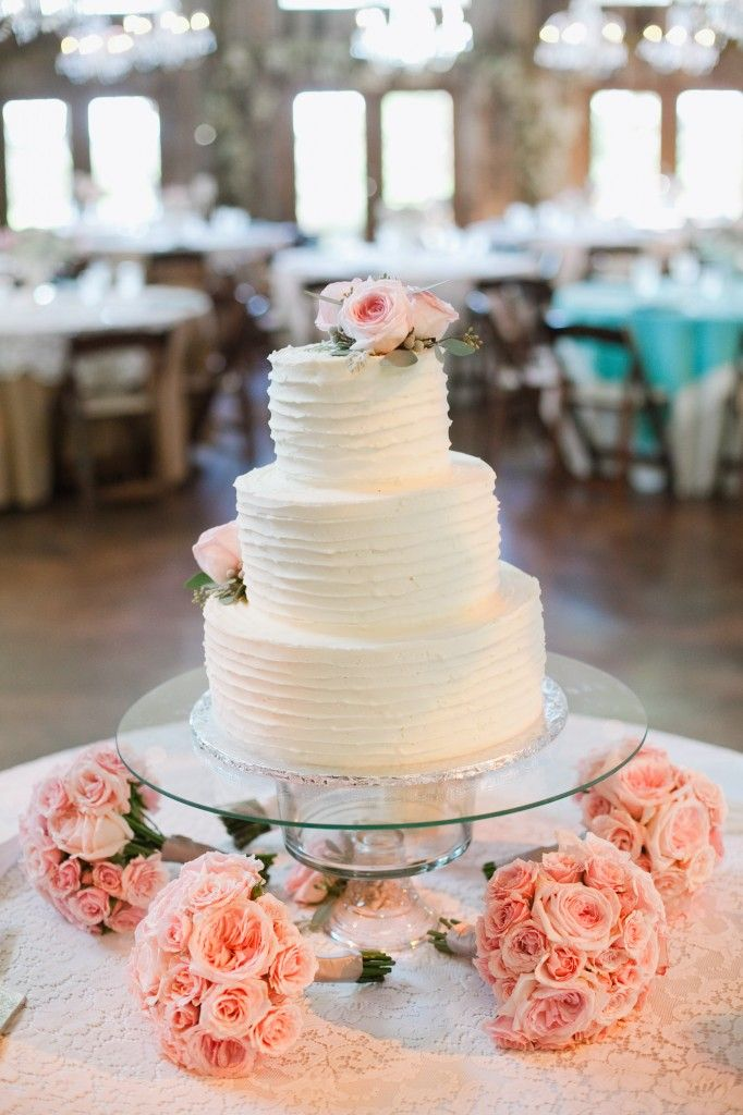 wedding cake display, bridesmaids bouquets under table. It looks like the cake stand is a punch bowl with a glass table top on top---pretty spiffy.