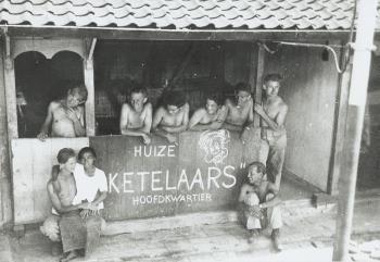 """Groepsfoto. Acht mariniers en een inlandsevrouw poseren voor een hut waarop staat """"Huize Ketelaars"""", Hoofdkwartier, Goebangkazerne te Soerabaja, Nederlands-Indie. 1948 .  (source Maritiem Digitaal NL)"""