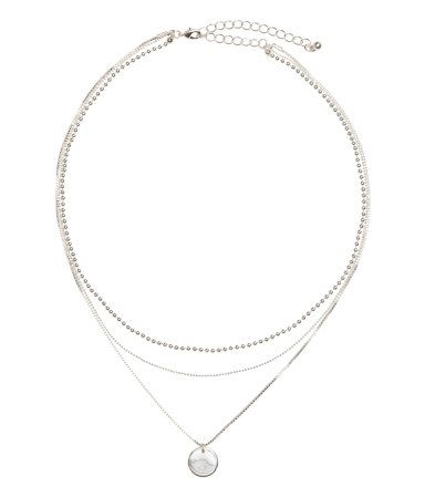 Silver-colored. Short, triple-strand necklace with metal chains in various designs, the longest chain with a round pendant. Adjustable length, 16 1/2 - 19 1