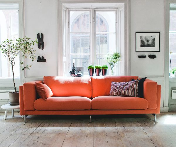 Orange Couch In A White Living Room Whith Bright Wood Floor