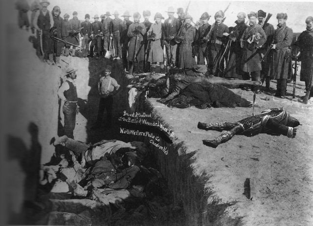 Mass grave at the Wounded Knee massacre. On 15 December 1890 Sitting Bull was shot & killed. On December 28, 1890, units of the U.S. Seventh Cavalry captured a group of Minneconjou Sioux Indians at Wounded Knee Creek in southwestern South Dakota. The next day, as the Indians surrendered their weapons, a shot rang out & the cavalry opened fire. At least 153 of the Sioux were killed (some estimate 300, out of about 350) - most of them women, children & unarmed men.
