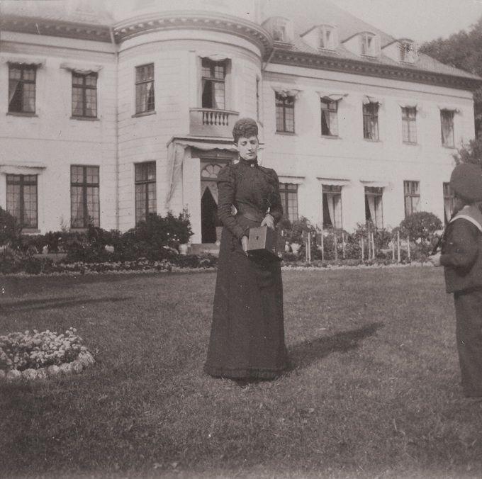 Будущая королева Великобритании Александра на фоне дворца с фотоаппаратом в руках. Бернсторф  » Нажмите для увеличения