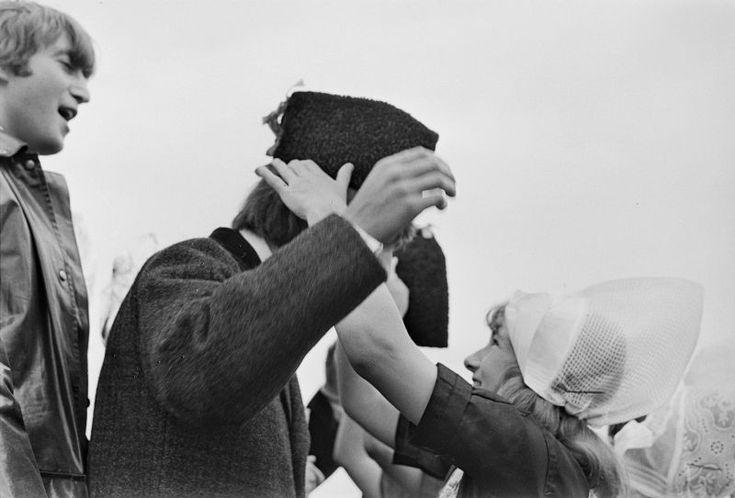BIJ HUN AANKOMST OP SCHIPHOL KREGEN DE BEATLES VAN IN VOLENDAMS COSTUUM GEKLEDE MEISJES VOLENDAMMER MUTSEN AANGEBODEN. EEN VAN DE MEISJES KROONT GEORGE HARRISON TOT TIENERHELD NUMMER EEN. 1964 #NoordHolland #Volendam
