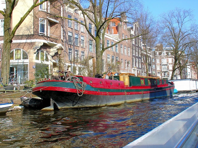 Brightly colored canal boats line Amsterdam s storied
