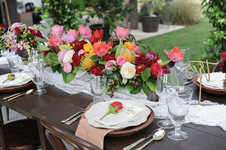 Spanish inspired wedding reception table centerpiece with red and white roses, tulips, prolea pincushin, snapdragon, poppy, king protea, ranunculus and hypericum berry by The Flower Girl. Photo by Jessica Frey Photography.