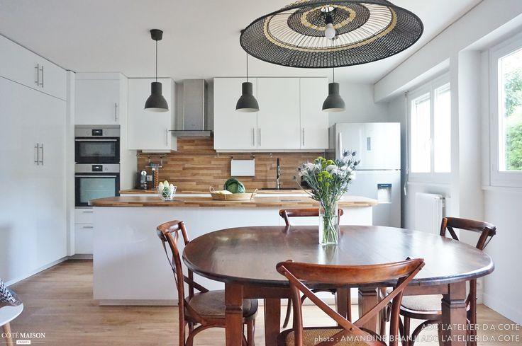 Une cuisine ouverte sur la salle à manger, toute de blanc et de bleu