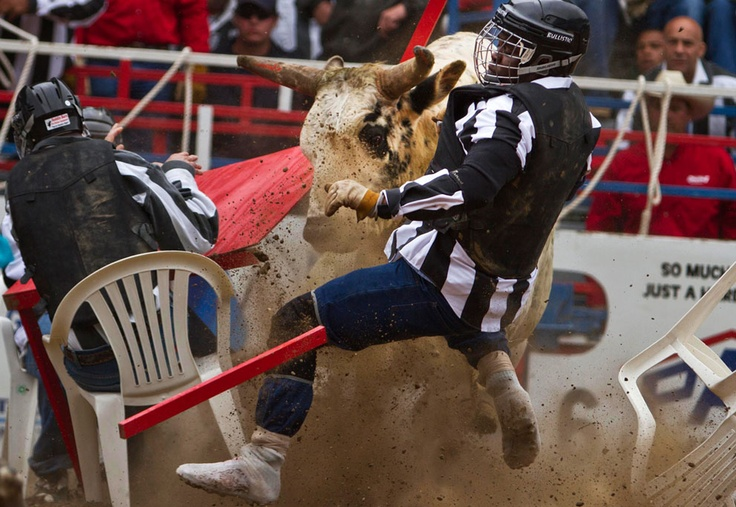 """Inmates are charged by a bull during """"Convict Poker"""" at the Angola Rodeo, a prison rodeo at Louisiana State Prison in Angola, Louisiana, on April 21, 2012. """"Convict Poker"""" is a game that involves four inmate cowboys who sit at a table in the middle of the arena with their hands on the table, and a wild bull is released, leaving the last man remaining seated, as the winner. The Angola Rodeo was first held in 1965 and features prisoners and staff competing in events ranging from bareback horse…"""