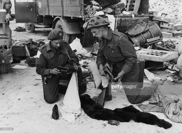 Canadian soldiers rummage through supplies left by the Germans in Normandy during World War II, 1944. Sapper J. A. Morreau and Corporal C. E. Cusack discover a pair of lady's shoes and a fur wrap.