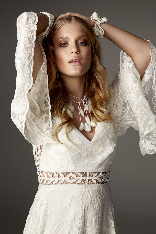 Hunter gown from Rue De Seine Love Spell Collection. The whimsical kaftan inspired Hunter gown is for the fancy-free bride. Nipped in at the waist with trim detail backed in nude nylon mesh, gives the illusion of a bare midriff and defines the waist. Full raglan sleeves, full silk embroidered skirt with a split up the centre front. These details as well as dramatic train show the relaxed nature of the gown and the bride wearing it. Perfect for the boho bride.