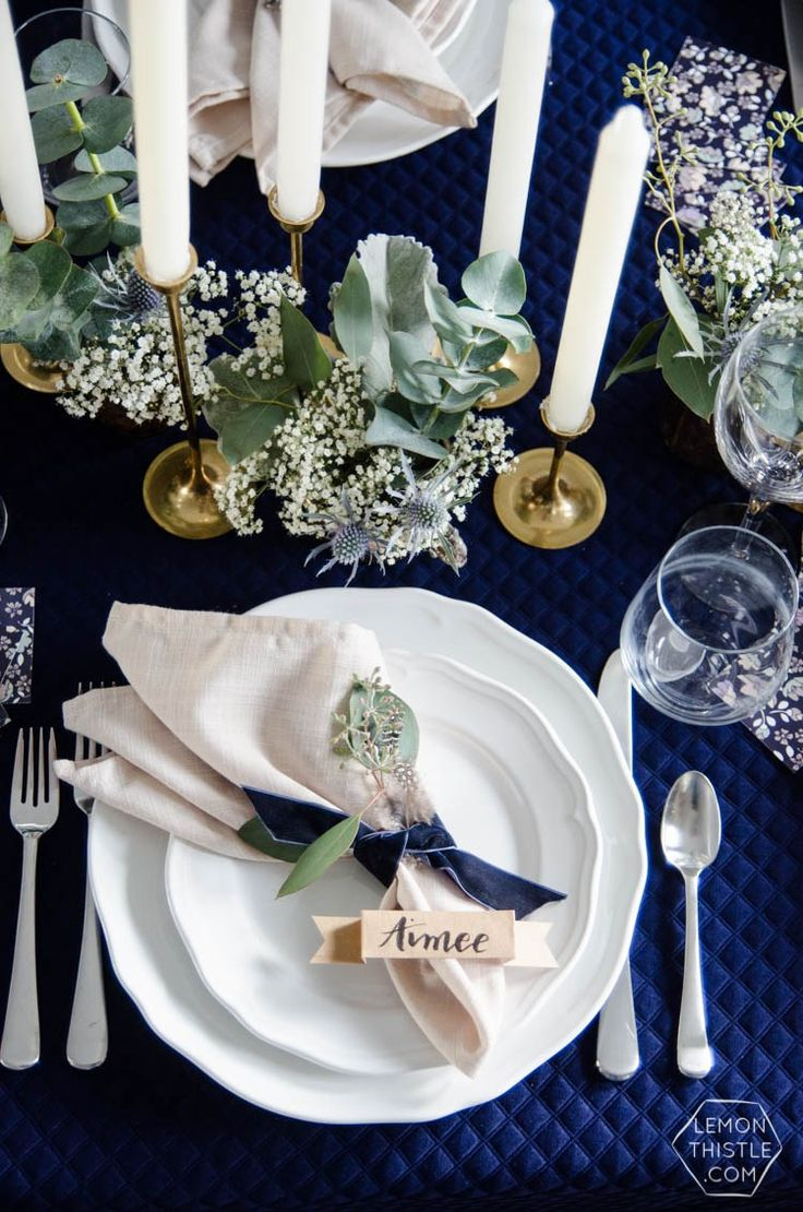 Napkins tied with velvet ribbon in pretty navy and white tablescape with white plates, gold candlestick holders, and leafy greens