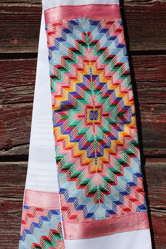 This white clergy stole has a unique rainbow design. The rainbow fabric has a great texture and appears woven. It is upcycled from a vintage, handmade cloth found at a local Christian thrift store. It is 5 1/2 inches wide and 51 inches long.  The curve of the neck makes it sit well and stay in place. It is medium-weight. This stole is reversible, with an elegant, subtly striped white back. This stole is a unique work of art, with the design lower on one side and higher on the other. It c...