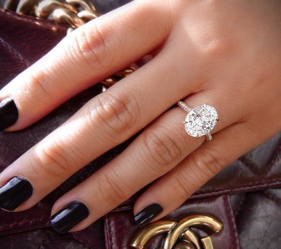 Platinum Engagement Rings to Love for a Lifetime | This large platinum engagement ring also boasts a lot of glamour. Check out the size of that oval center diamond, beautifully set on an eternity band studded with more hardware.