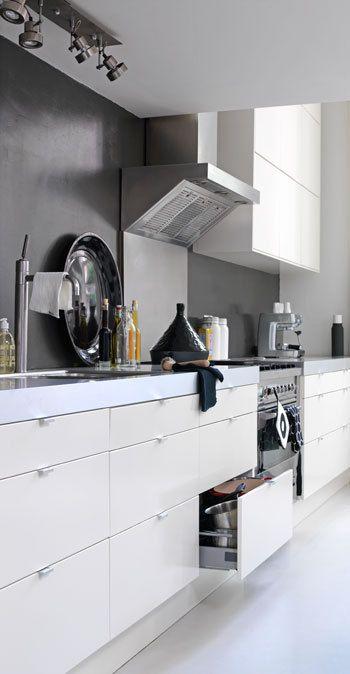 #47. Small white kitchen with black splash back.