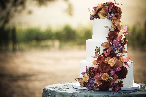 Dress up a classic white fall wedding cake with a cascading flowers and butterflies