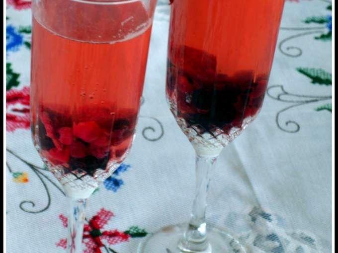 Num jarro misture o champanhe com a gasosa. Adicione o açúcar amarelo e os paus de canela. Mexa bem com uma colher de pau, até dissolver o açúcar. Junte os frutos vermelhos e reserve durante 5 minutos. - Receita Bebida : Sangria de champanhe e frutos...