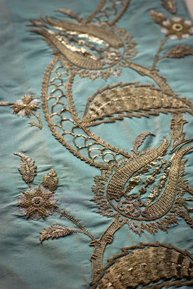 Our couture fabric, Tuana is an elegant and exotic leading edge design based on classic Persian motifs. Plants climb and entwine, forming a lovely leading edge design. The flowers and leaves are hand embroidered in various shades of gold to create a beautiful texture, and iridescent shine. Pictured here is the Tuana couture fabric on Orissa Dupion,  Sea Spray.