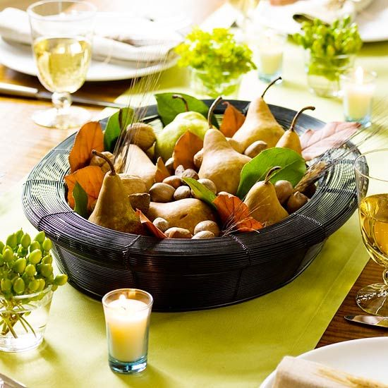 Tuck pears, nuts and leaves in a wire basket for a fresh cornucopia look. Get more centerpiece ideas from BHG.com.