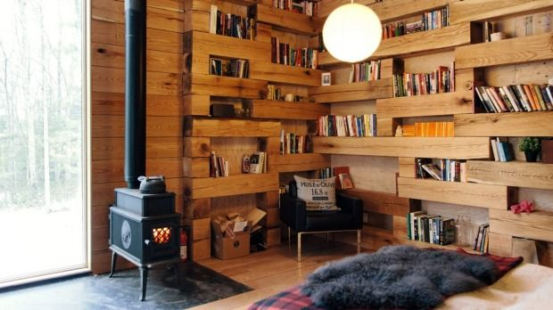 A tiny booklined library in the wood makes a perfect reading retreat
