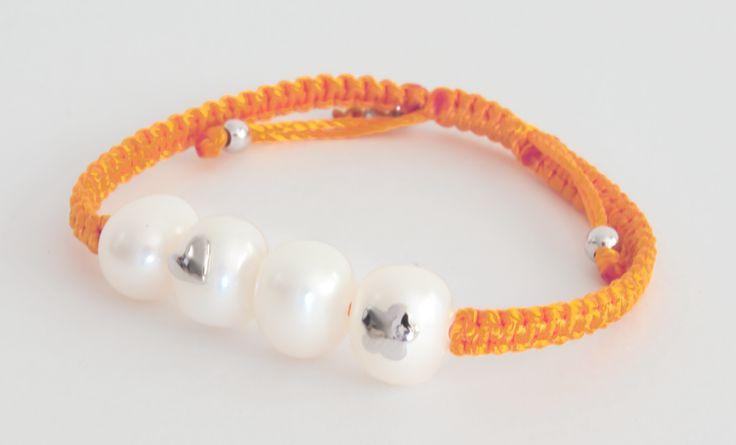 Pulsera tejida en macramé de color naranja con cuatro perlas blancas, con dos incrustaciones en plata, una en forma de flor y otra en forma de corazón.