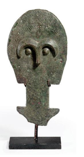 Anatolian bronze idol, 2nd millenium B.C. Stylized anthropomorphic votive with an ovoid head on a rectangular neck and projecting triangular arms, the face delineated on one side with m-shaped brows merging with the nose in high relief, pellet eyes below, the slit mouth incised, two rows of stippling arching above, one row curved up below, 17.3 cm high. Private collection