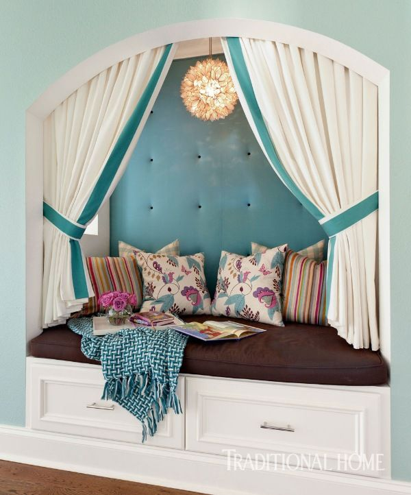 A reading nook in the hallway gets extra cushion with a tufted wall behind the teal-banded curtains. - Photo: Nancy Nolan / Design: Tobi Fairley