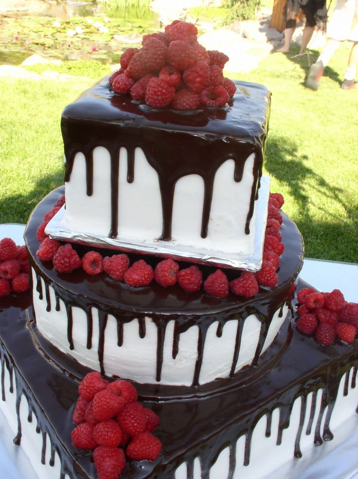 - This vegan wedding cake, with two chocolate cakes and one white cake, is filled with raspberry filling, frosted with buttercream and topped with drizzled chocolate ganache and fresh raspberries.