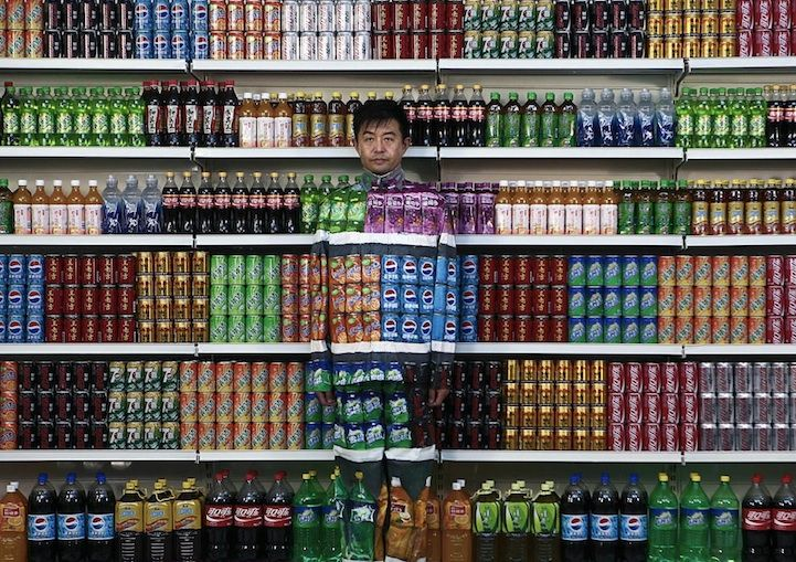 Liu Bolin paints himself, with the help of others, so that he seamlessly blends into rows of soft drinks.